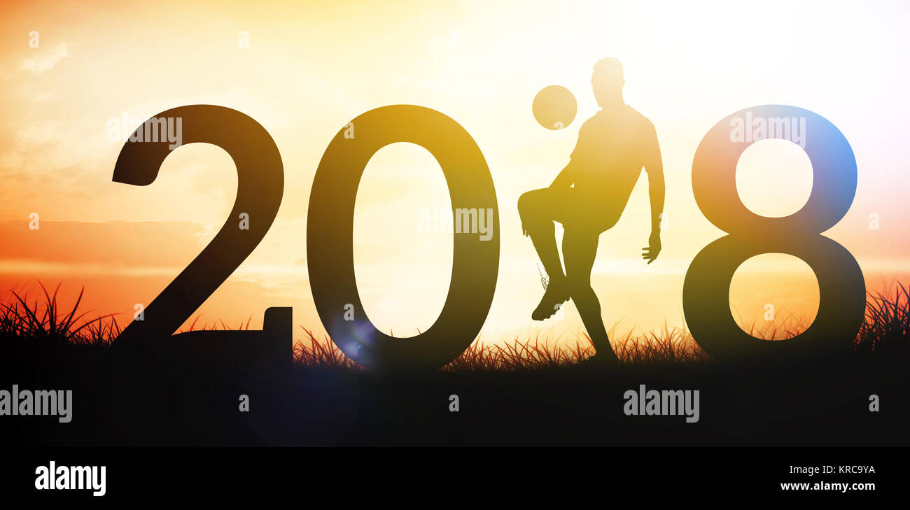 Silhouette of a soccer player  against orange sunrise - Stock Image