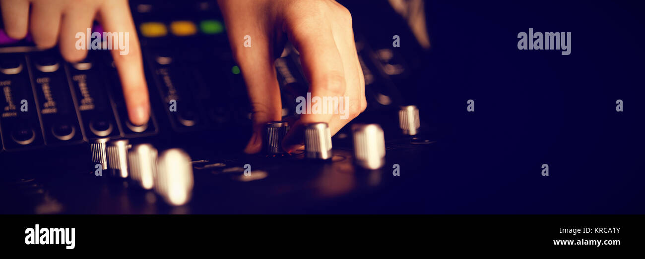 Cropped hands of audio engineer using sound recording equipment at recording studio Stock Photo