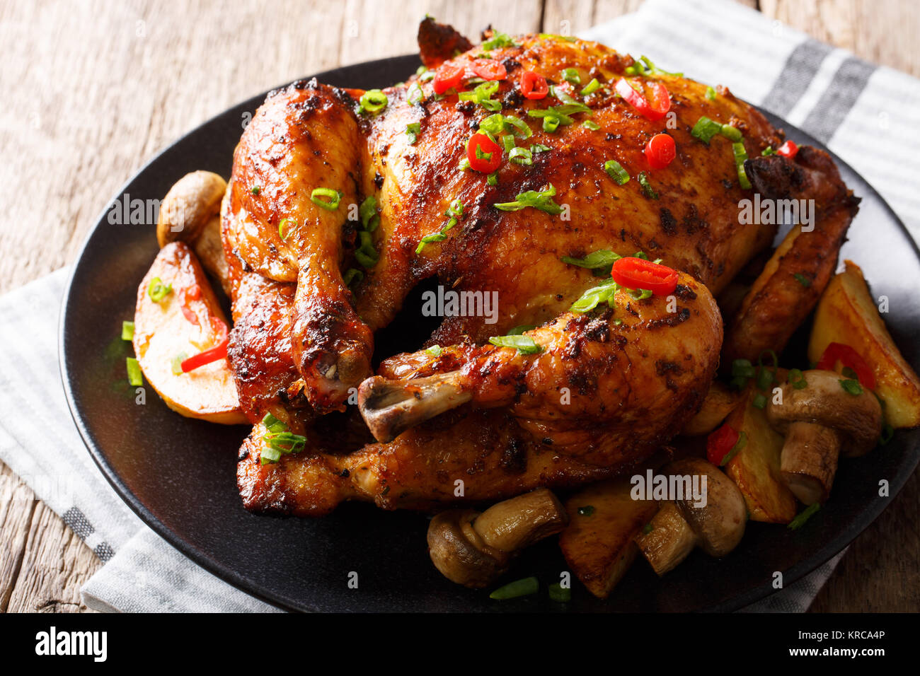 Festive food: fried chicken with mushrooms and potatoes close-up on a plate on a table. horizontal - Stock Image