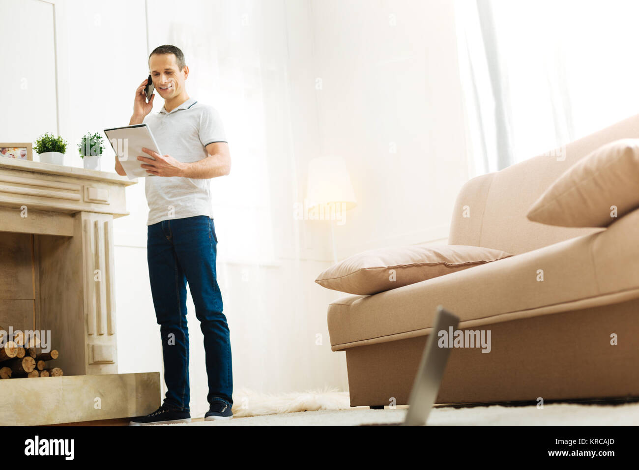 Calm cheerful man talking on the phone and looking at his notes - Stock Image