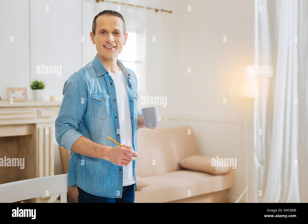 Positive cheerful engineer holding a pencil while drinking tasty tea - Stock Image