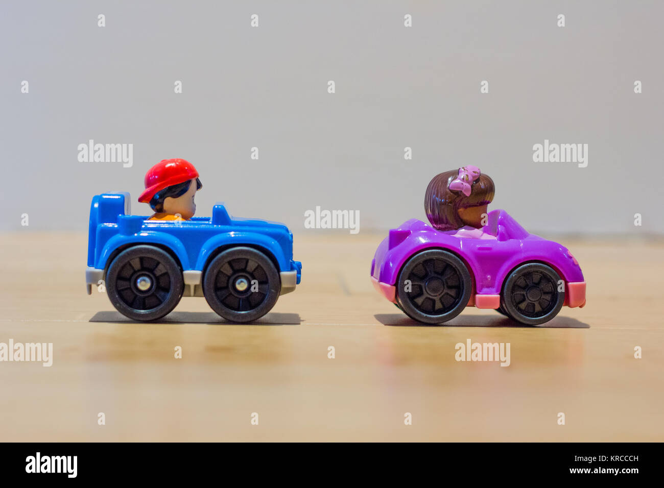 Two miniature toy cars on wooded floor with shadow reflection - Stock Image
