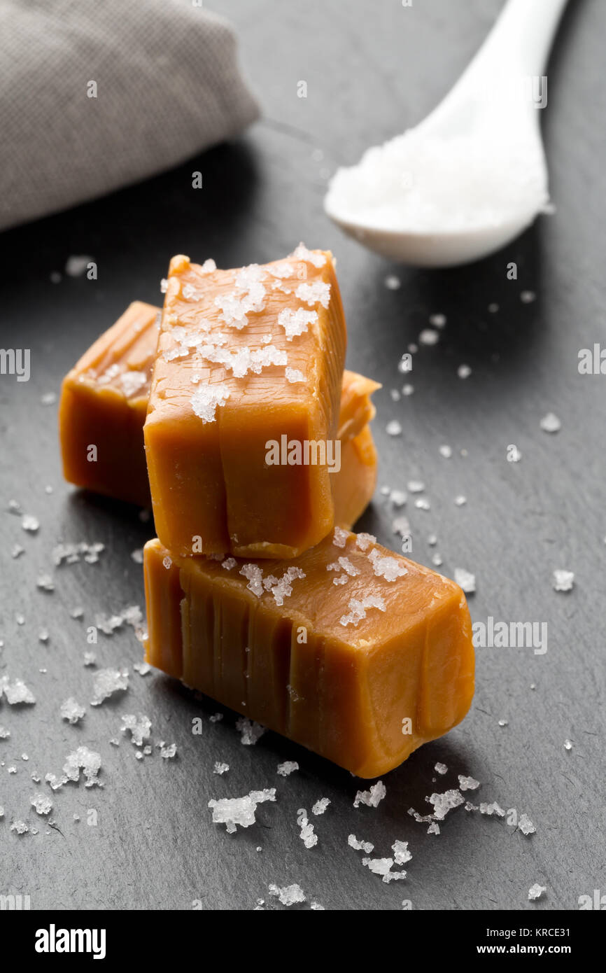 Hand made caramel toffee pieces with sea salt on kitchen stone plate background - Stock Image