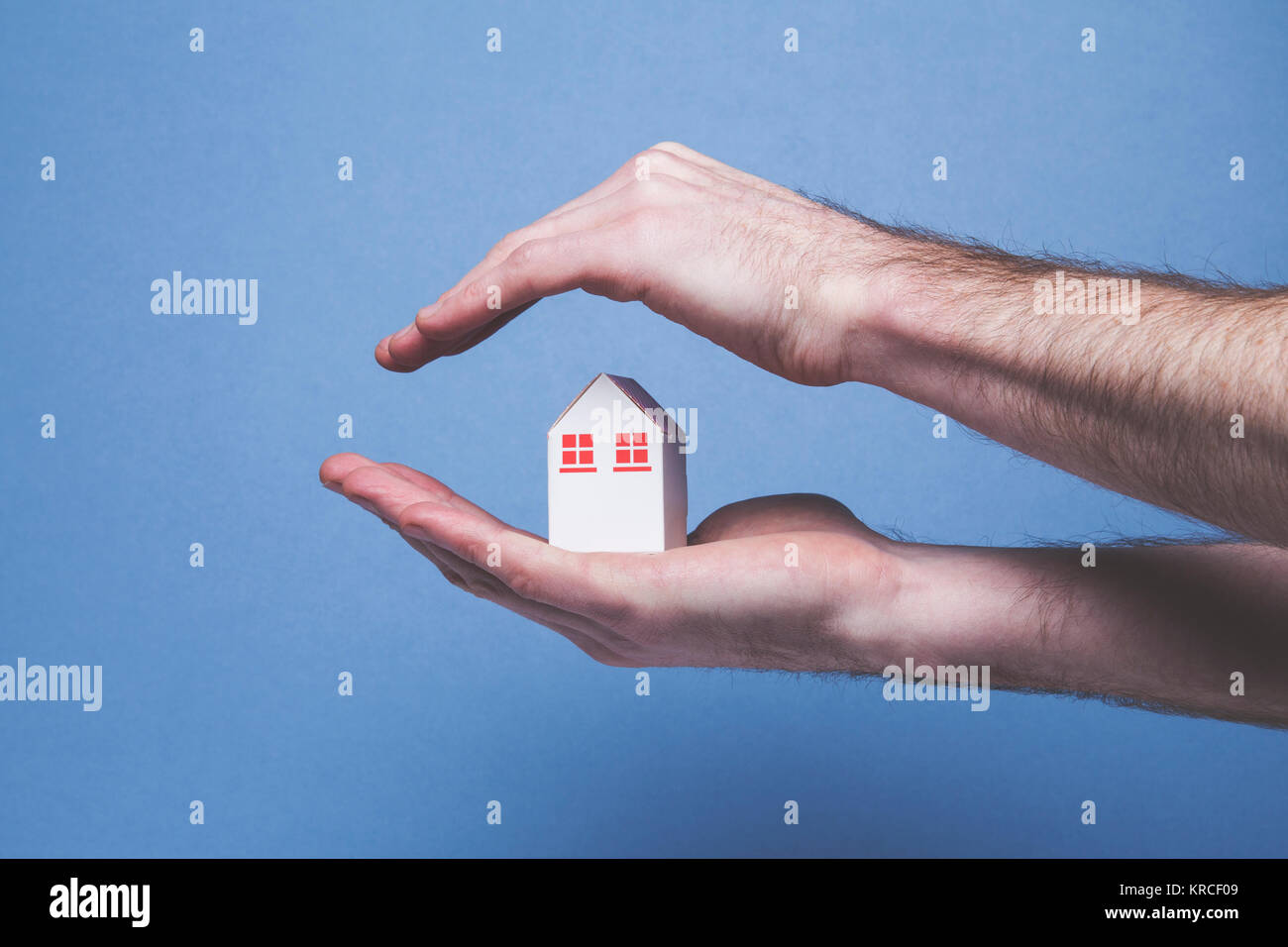Hands covering a toy house. Home protection concept Stock Photo