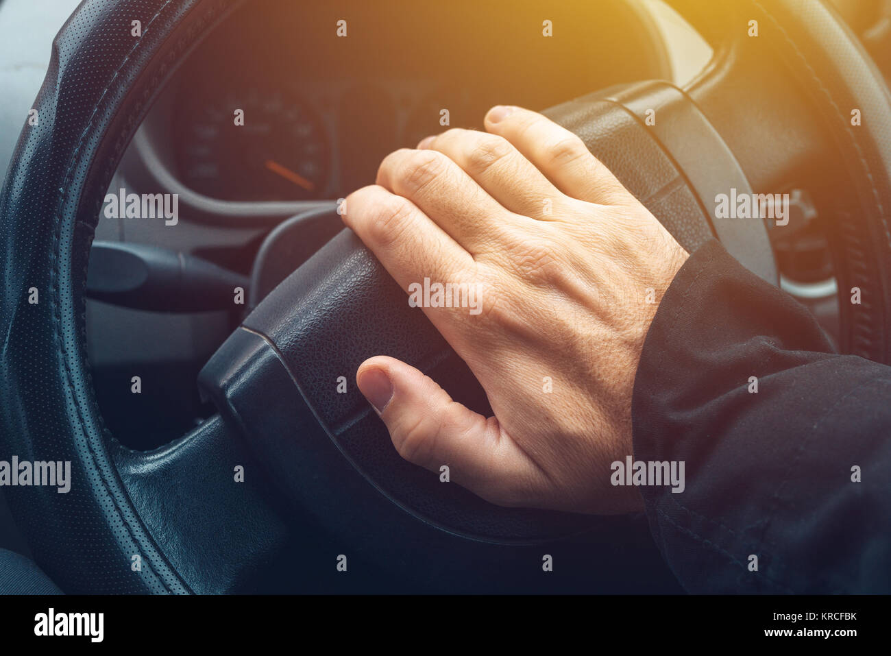 Male hand honking the car horn, man driving vehicle and beeping - Stock Image