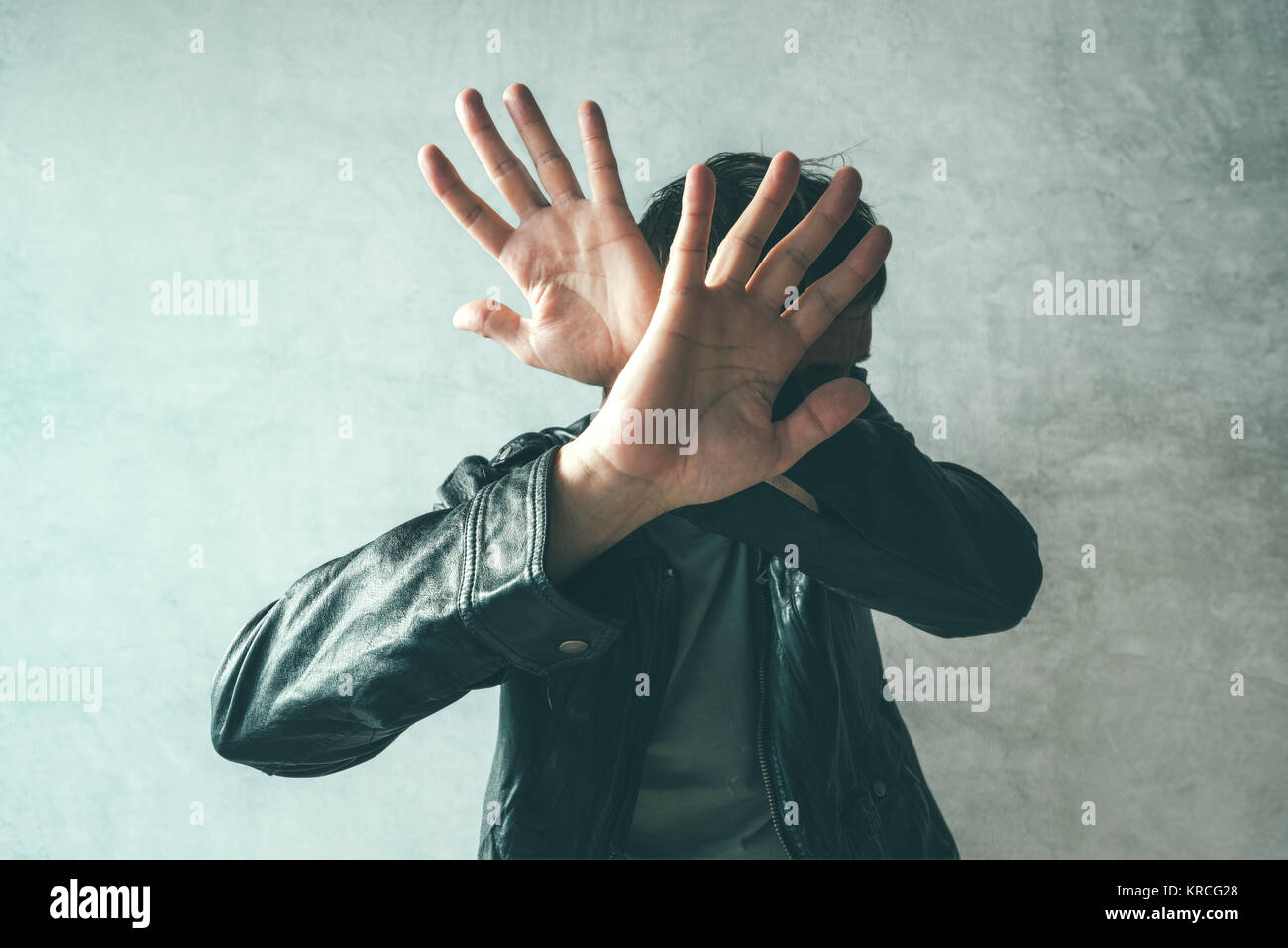 Male protecting face from violent attack. Adult caucasian man covering face and head to stop punches in a fight - Stock Image