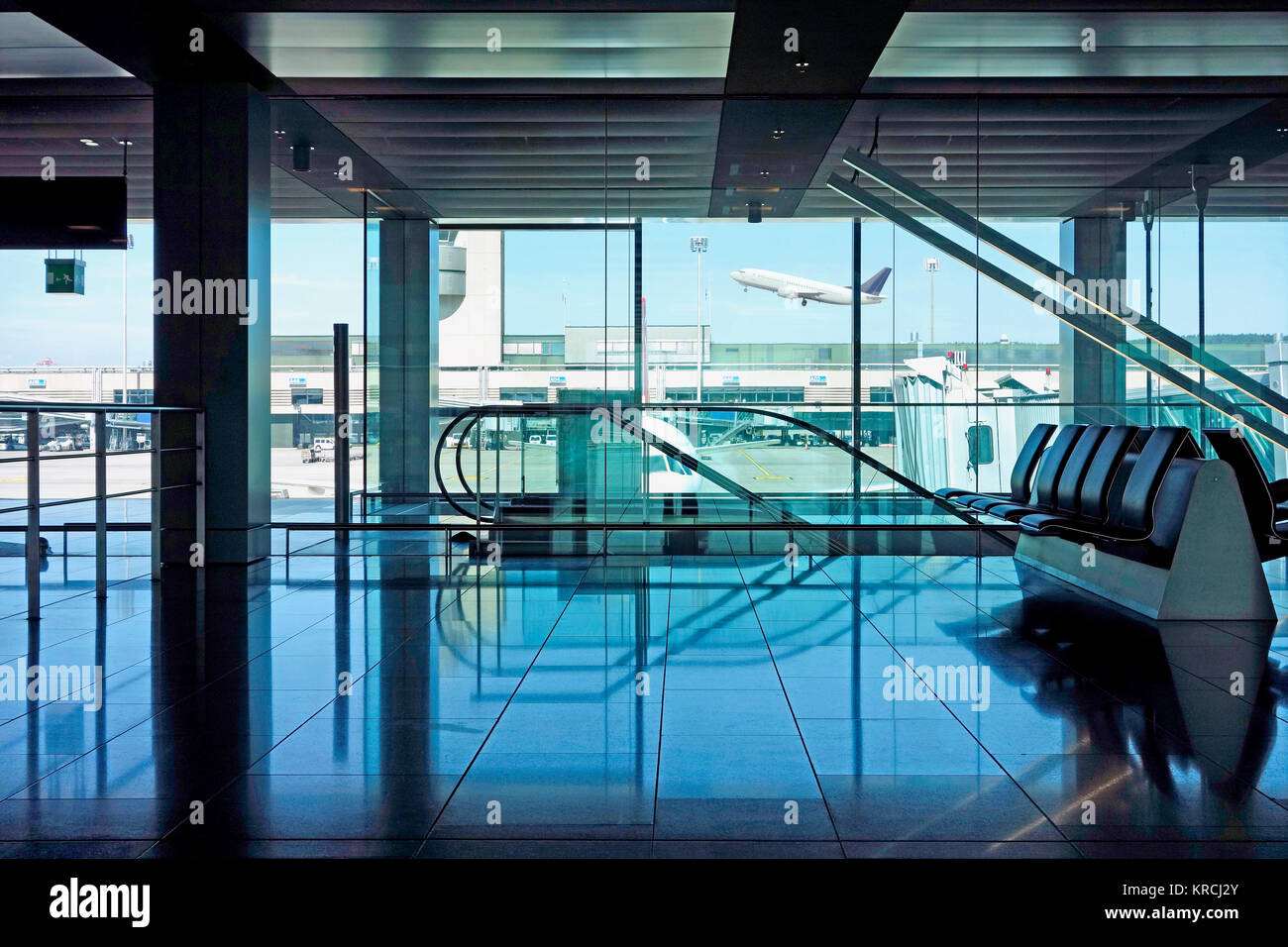 Empty Airport departure lounge with seating and escalators overlooking the runway with a waiting plane. - Stock Image