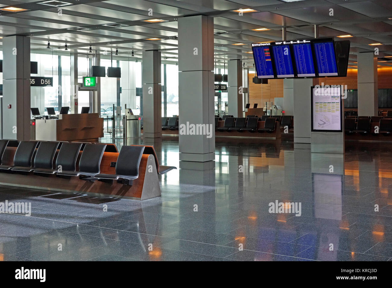 Empty airport departure lounge waiting area with flight information screens. - Stock Image