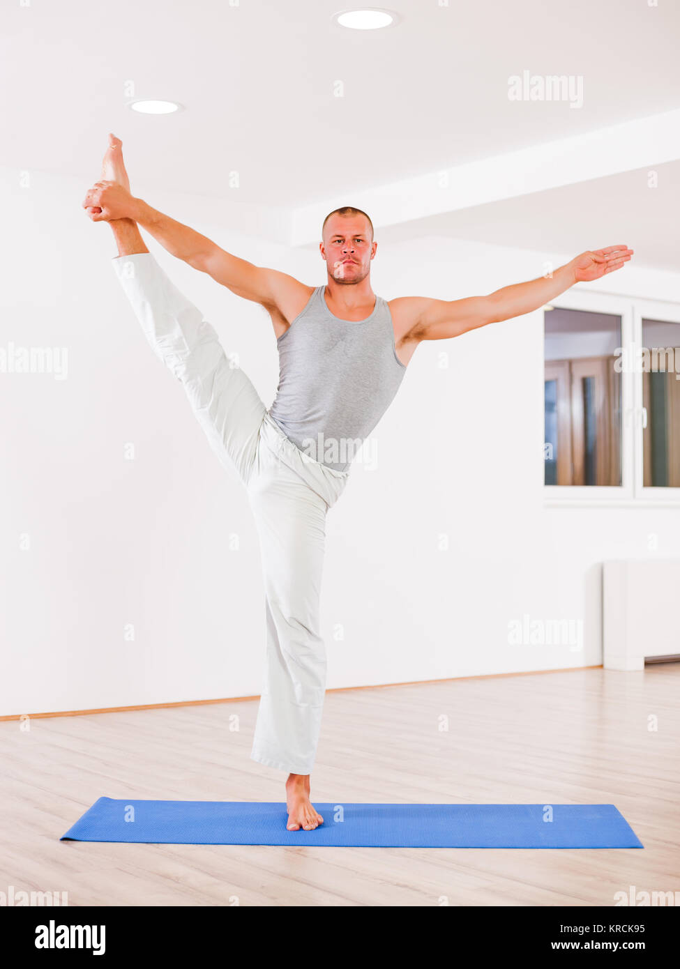 Adult man practicing yoga, Padangusthasana / Extended Hand To Big Toe Pose - Stock Image