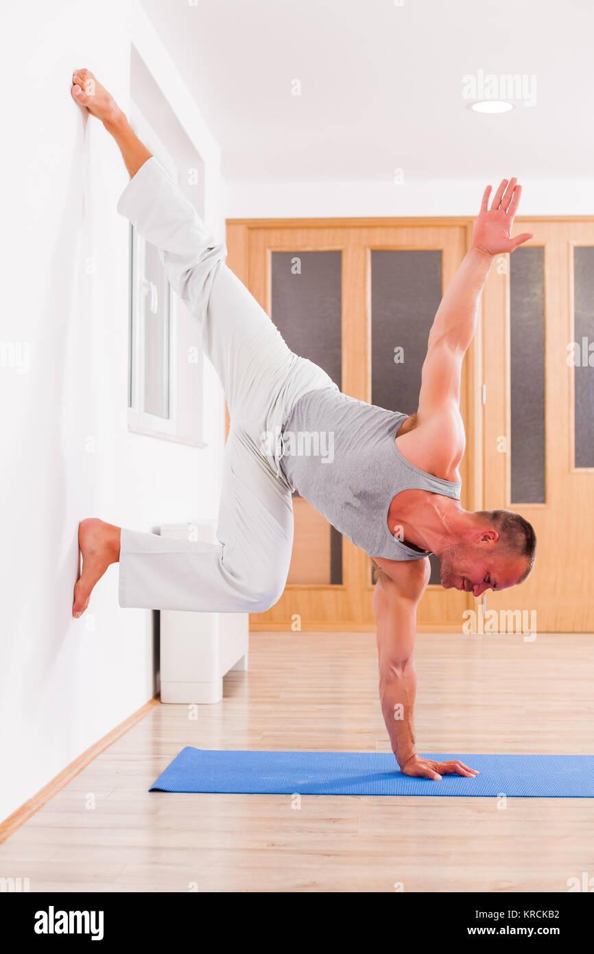 Adult man practicing yoga, Vrksasana / Handstand pose - Stock Image