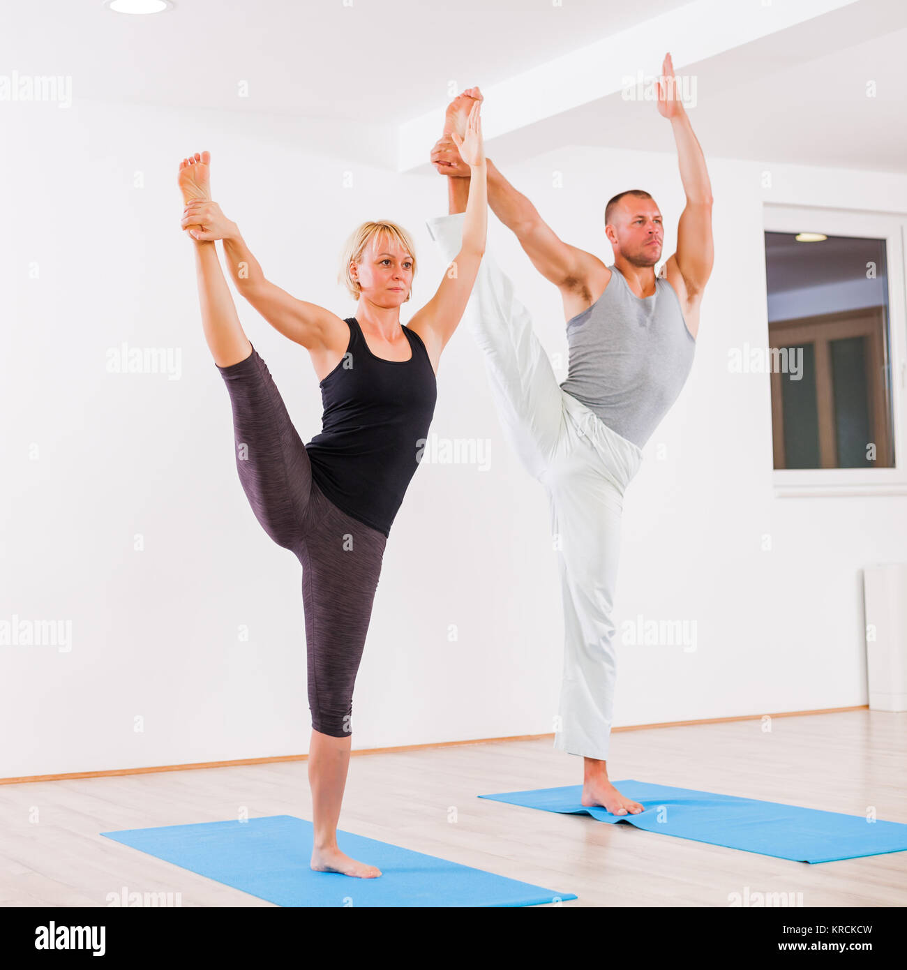 Adult man and woman practicing yoga, Padangusthasana / Extended Hand To Big Toe Pose - Stock Image