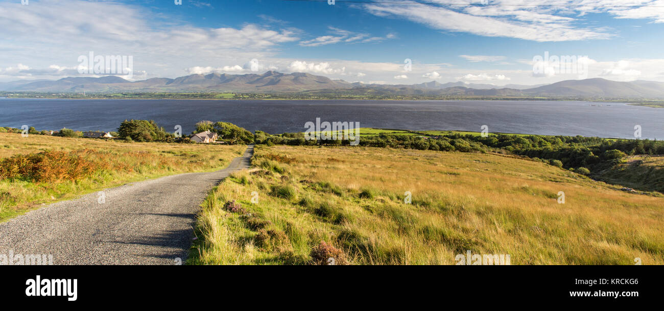 A narrow mountain pass road leads down the slopes of Caherconree mountain on Dingle Peninsula, with Dingle Bay and - Stock Image