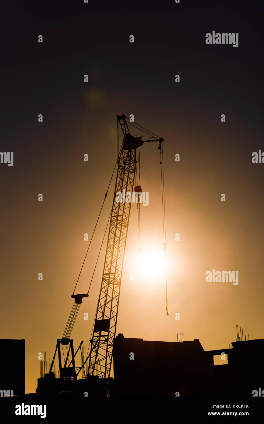 Tower crane on a construction site at sunset - Stock Image