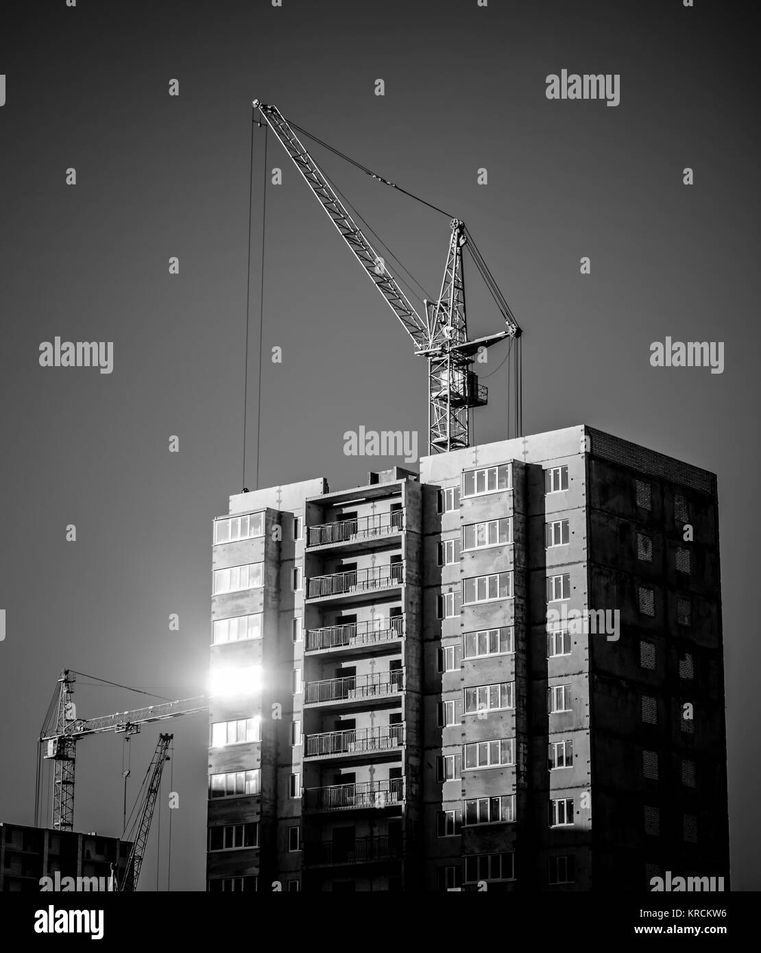 silhouettes of industrial construction cranes and building - Stock Image