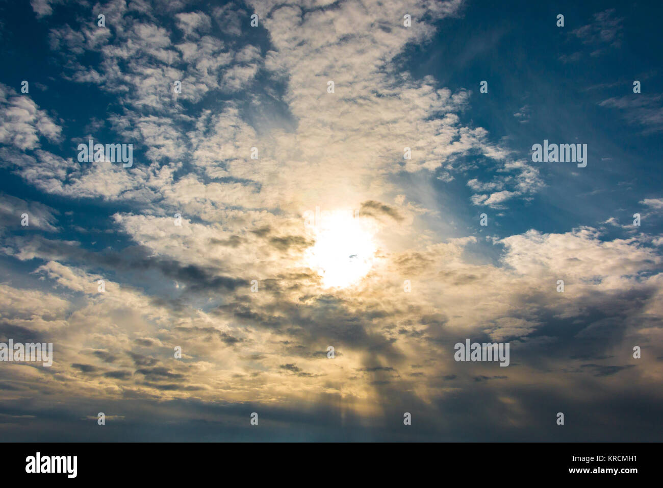 The sky full of white clouds and the golden sun - Stock Image