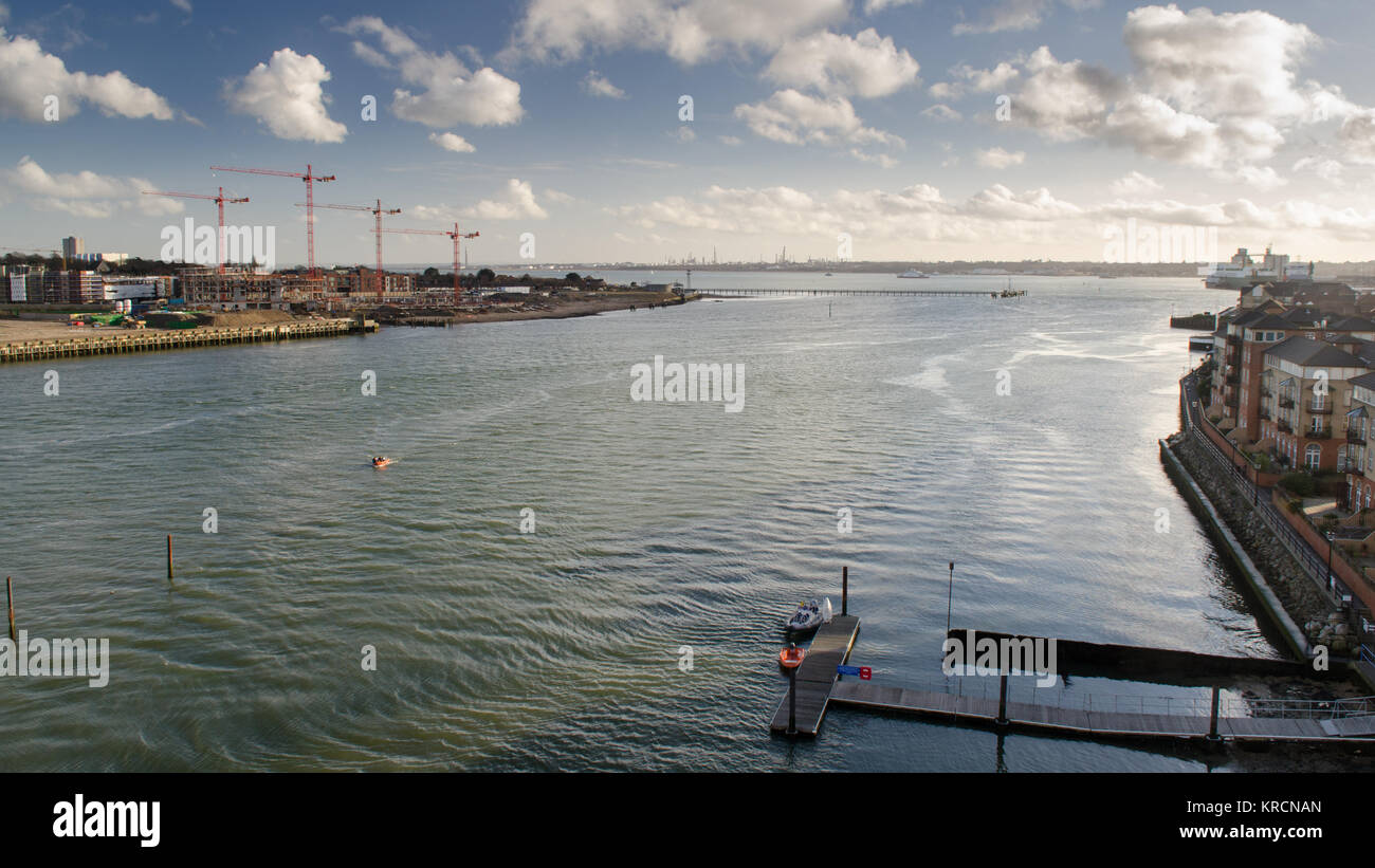 The River Itchen flows into Southampton Water between apartment buildings and construction sites in the city of - Stock Image