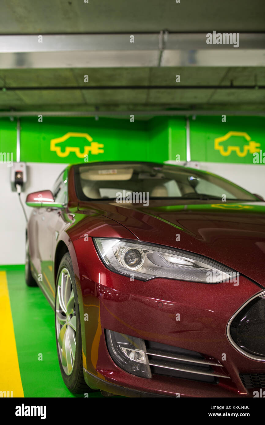 Electric car at a charging point in an underground parking (shallow DOF  color toned image) Stock Photo