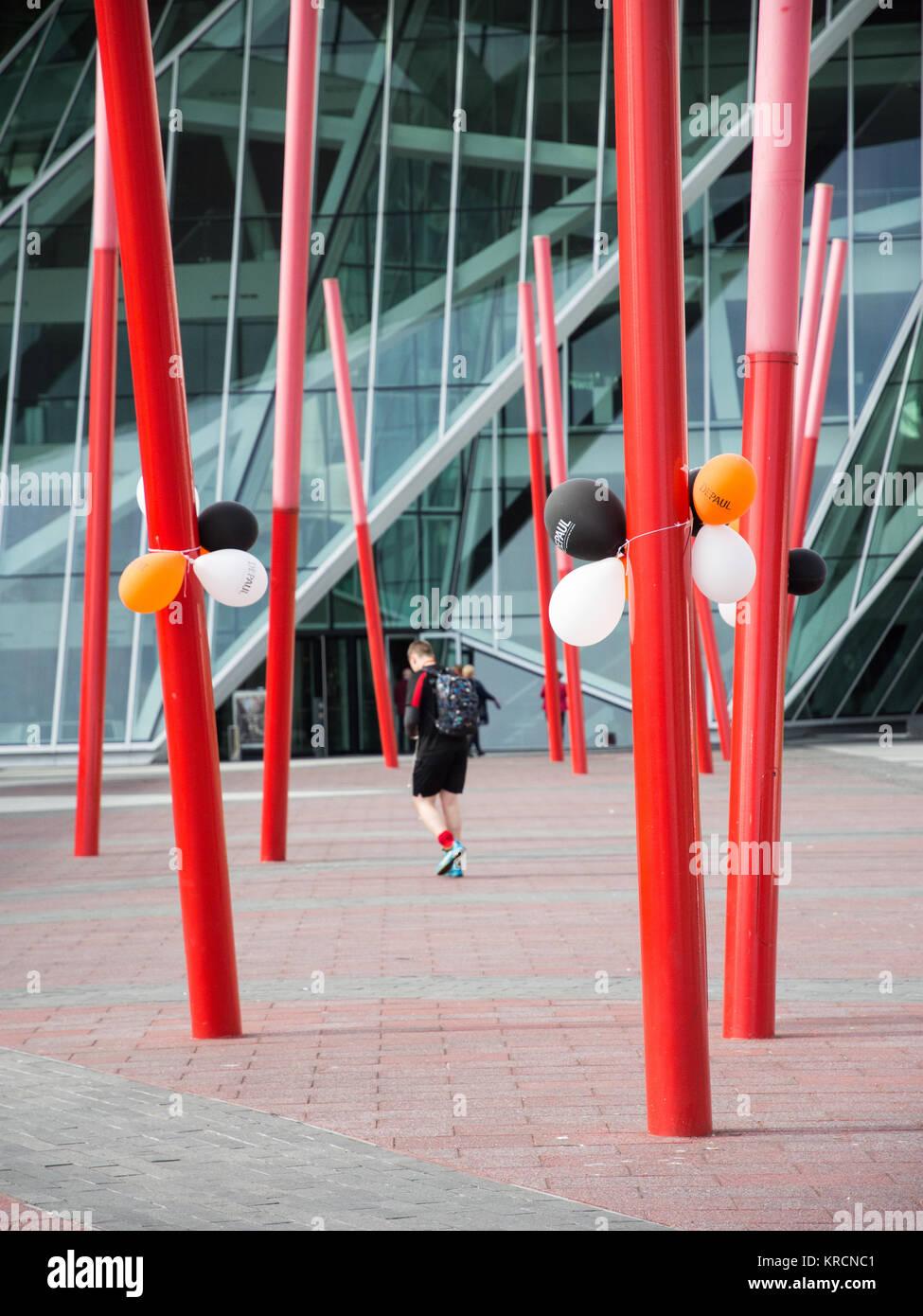 Dublin, Ireland - September 17, 2016: A pedestrian walks past sculptural poles and balloons outside Bord Gais Energy - Stock Image