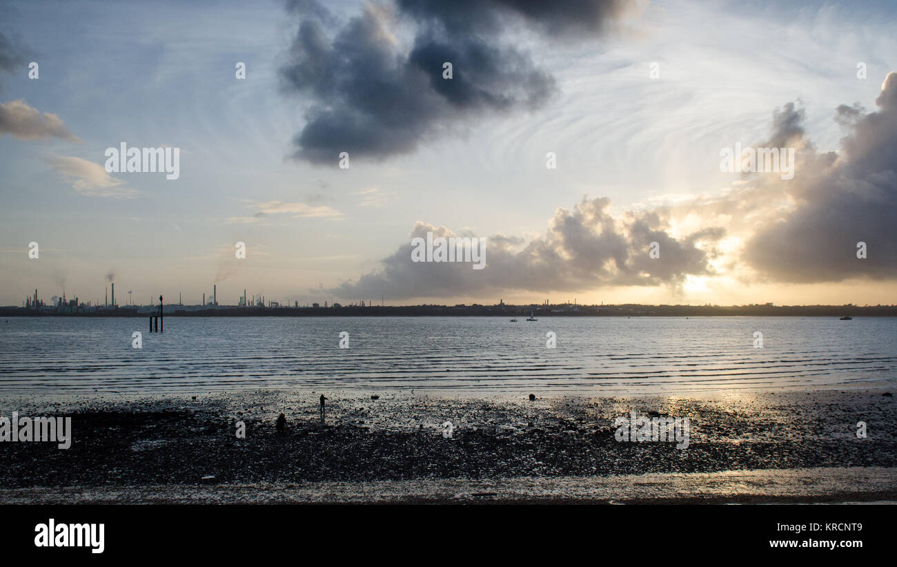 The sunset silhouettes the industrial towers of Fawley oil refinery on the shores of Southampton Water, seen from - Stock Image