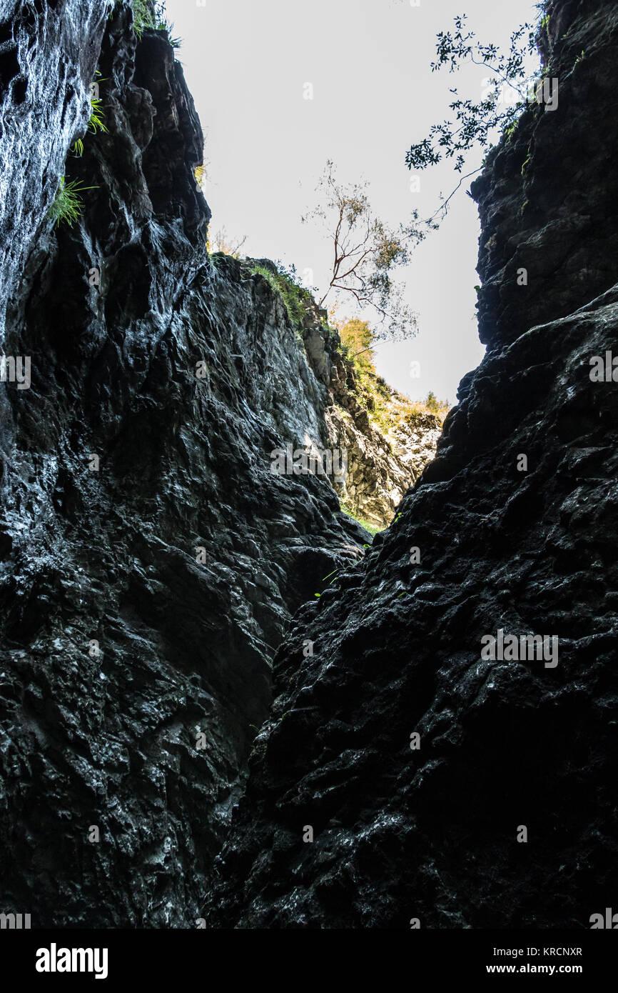 Huge black rocks and a dark deep canyon - Stock Image