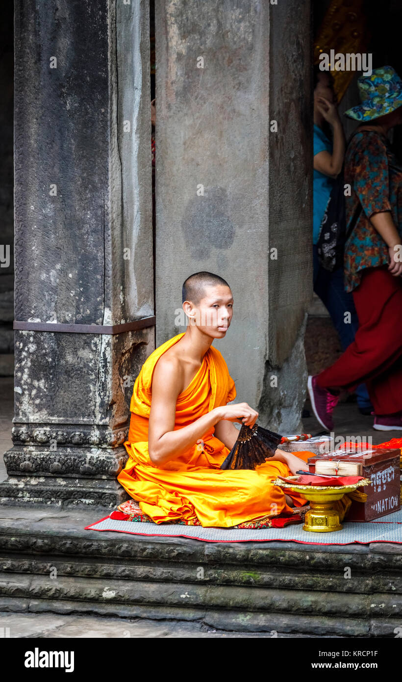 Young Buddhist monk in saffron robes sits in Angkor Wat, a temple complex near Siem Reap in Cambodia, the largest Stock Photo