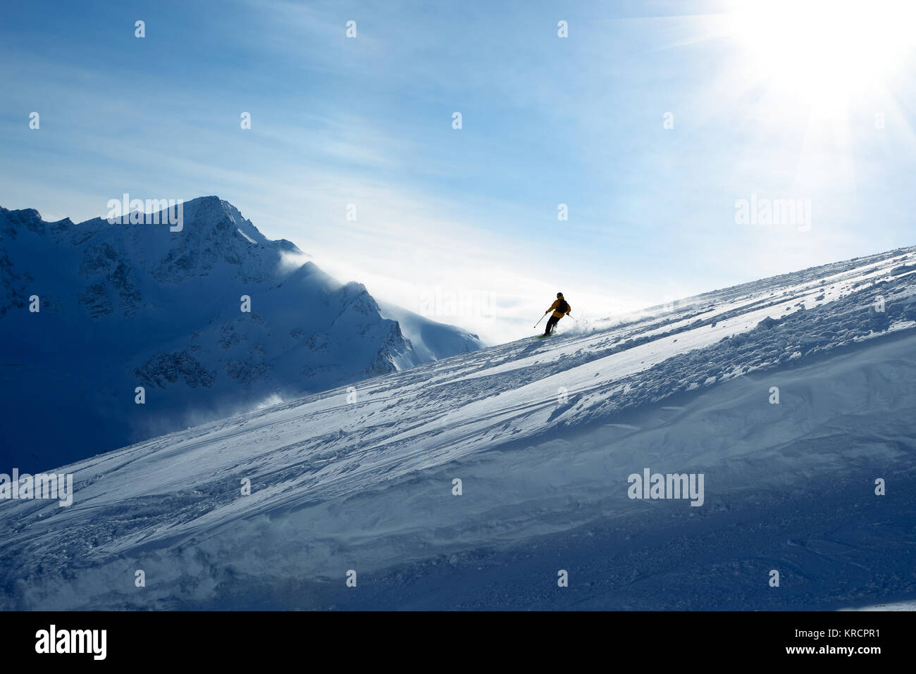 Skier going down the slope on a background of blue sky and mountains - Stock Image