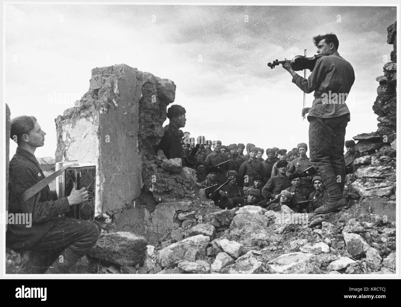 A musical interlude for Soviet soldiers amoung the ruins. Soldiers play the accordion and the violin. Date: 1942 - Stock Image