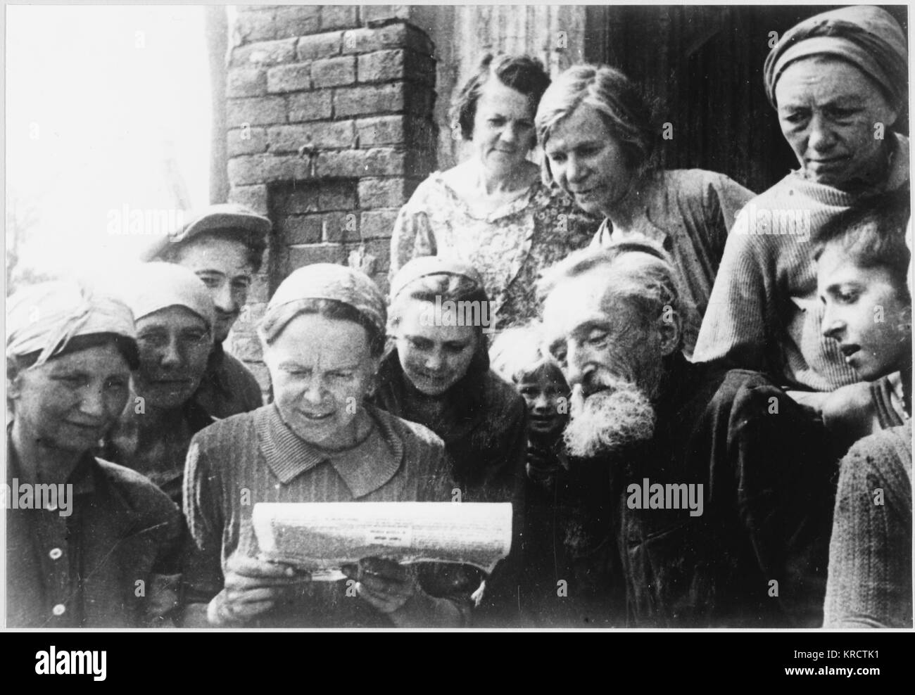 Civilians read news of the war. - Stock Image