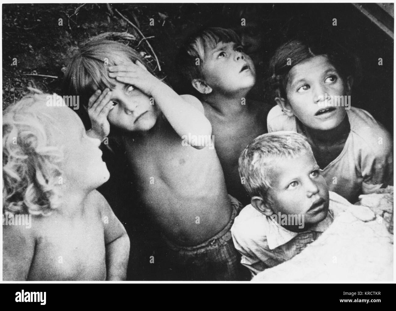 Children shelter in a slit- trench during a German air- raid on Moscow. Date: 1941 - Stock Image