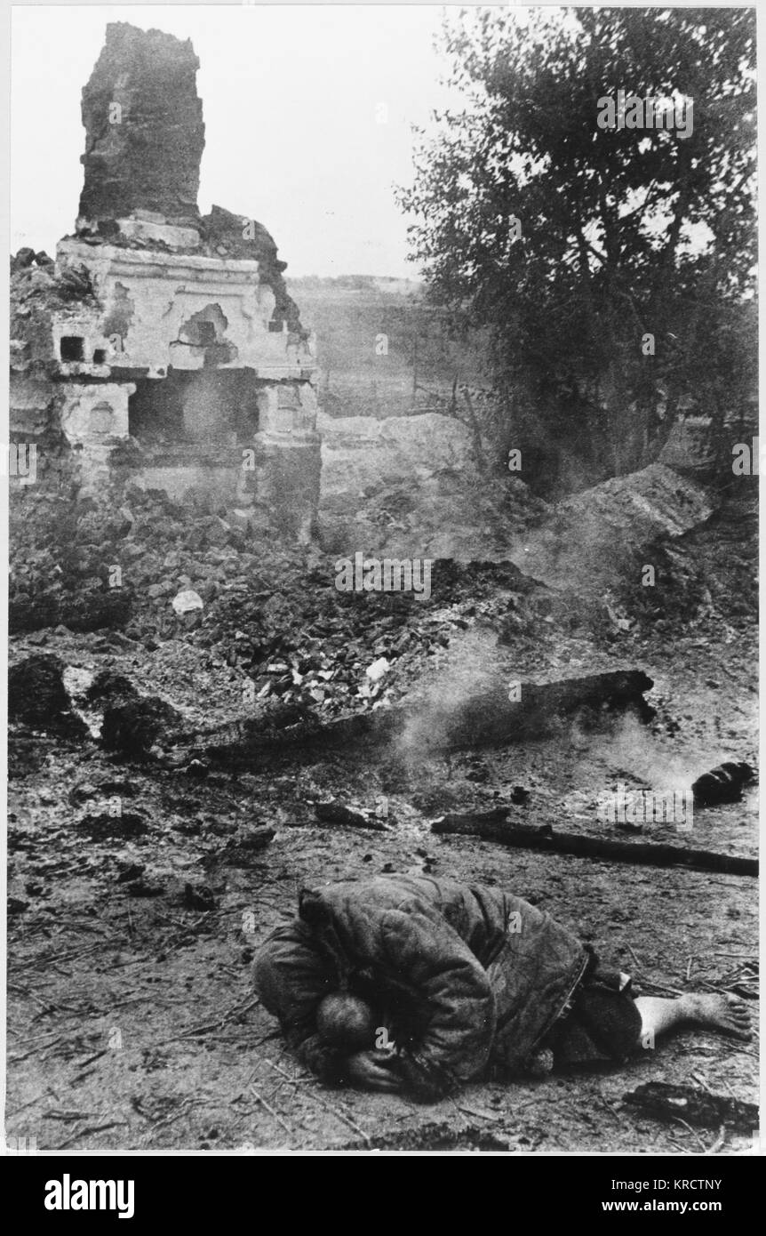In the Ukraine, a civilian weeps on the ground of a devastated village, which was once her home Date: 1941 - Stock Image