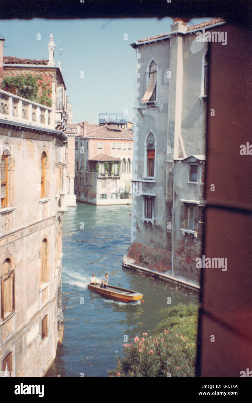 View of a canal through a window in Venice, Italy. Date: 1968 - Stock Image