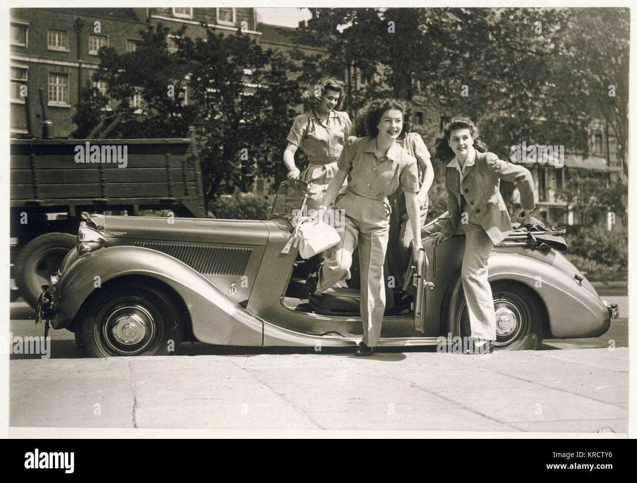 Four glamorous war-time women wearing trouser suits leap from an open top car Date: early 1940s - Stock Image