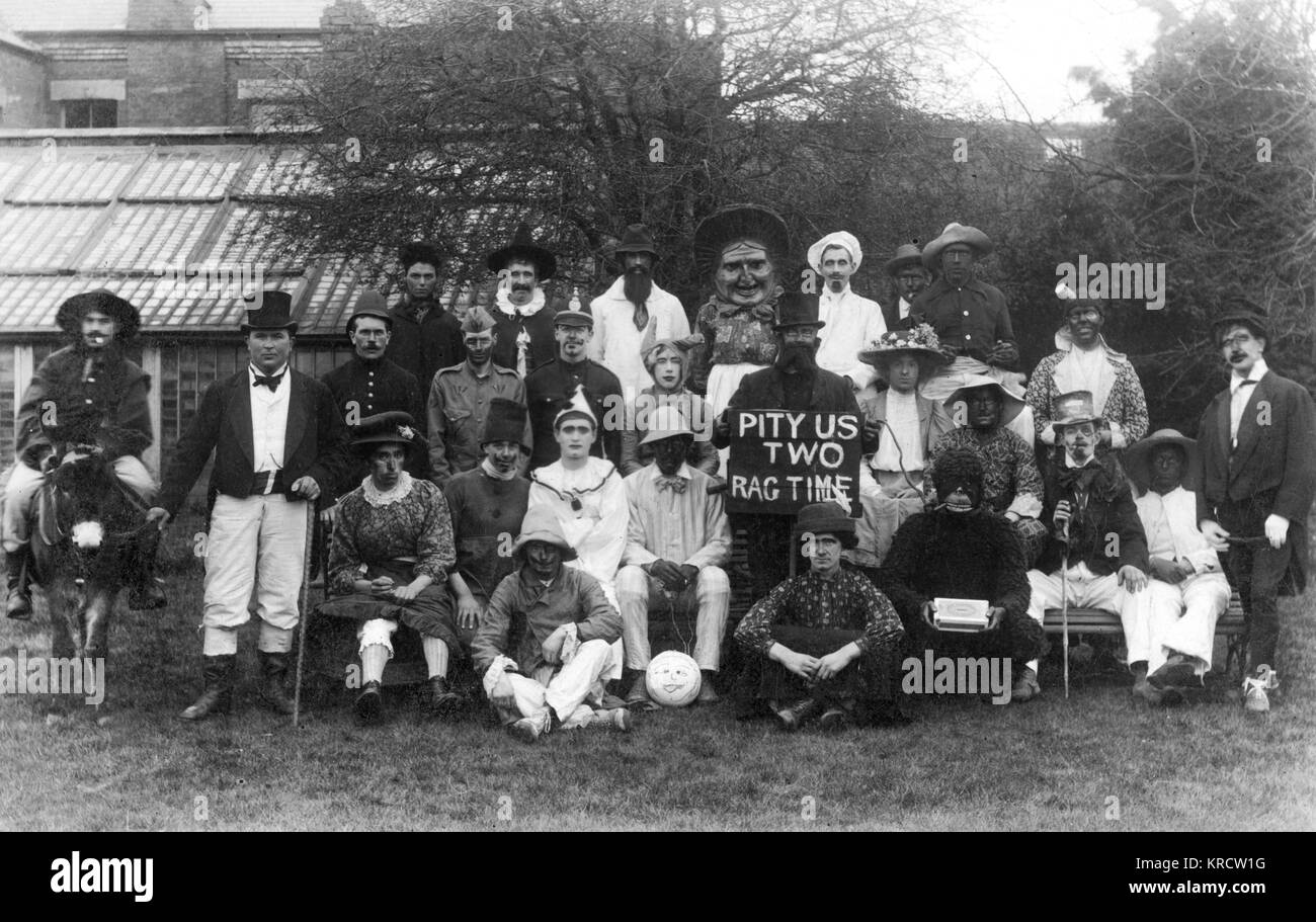 A group of people in ragtime style fancy dress, including a cowboy on a mule, two policemen, men in drag, a pierrot, - Stock Image