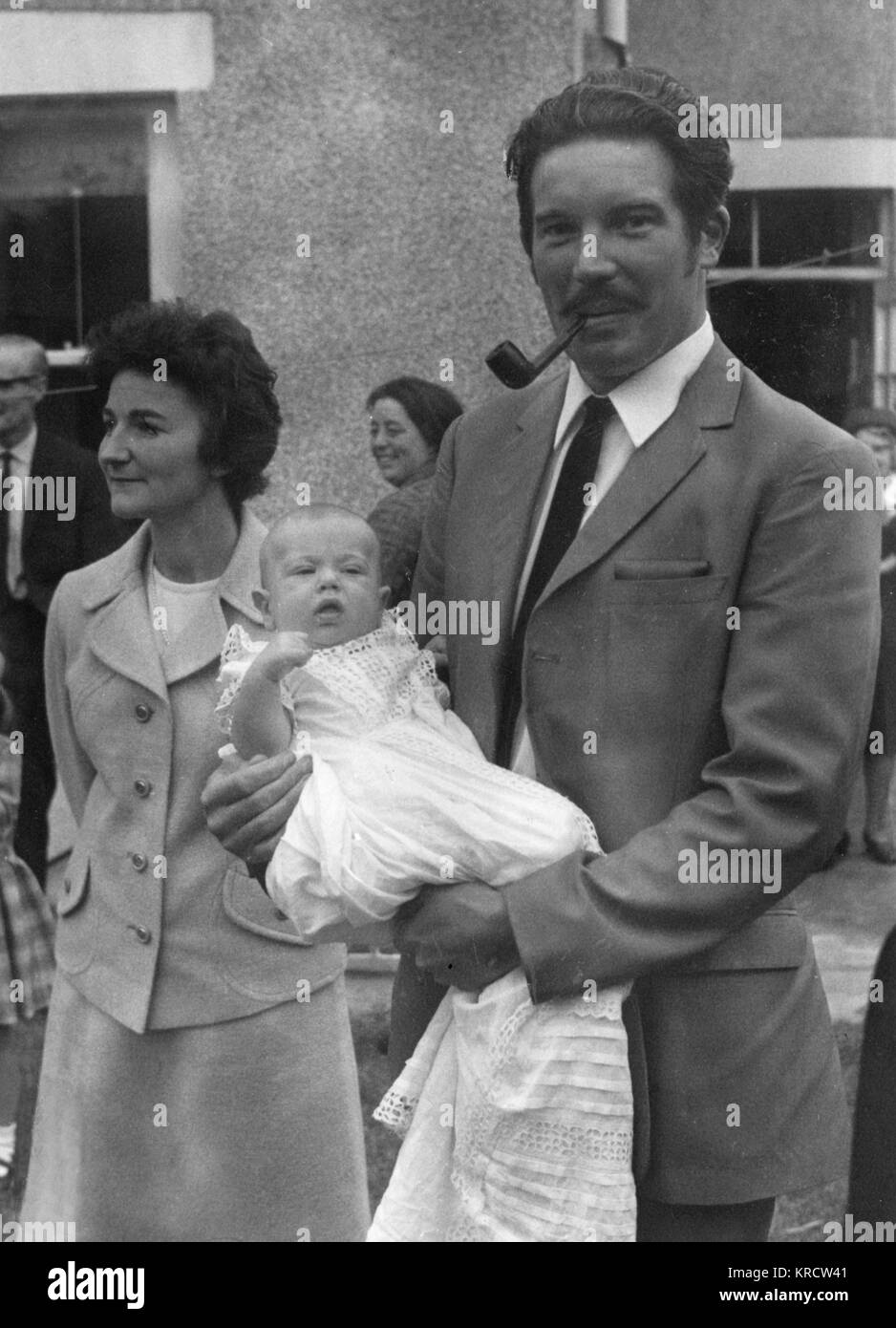 The versatile godfather at a christening manages to hold the baby and smoke his pipe at the same time! Date: circa - Stock Image
