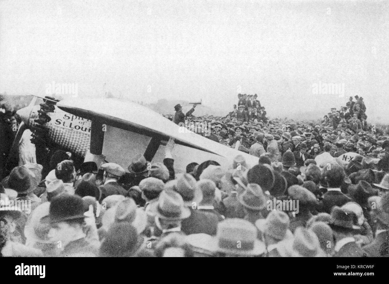 Thousands swamp around the 'Spirit of St. Louis' as the plane lands at Croydon, London. Date: 1927 - Stock Image
