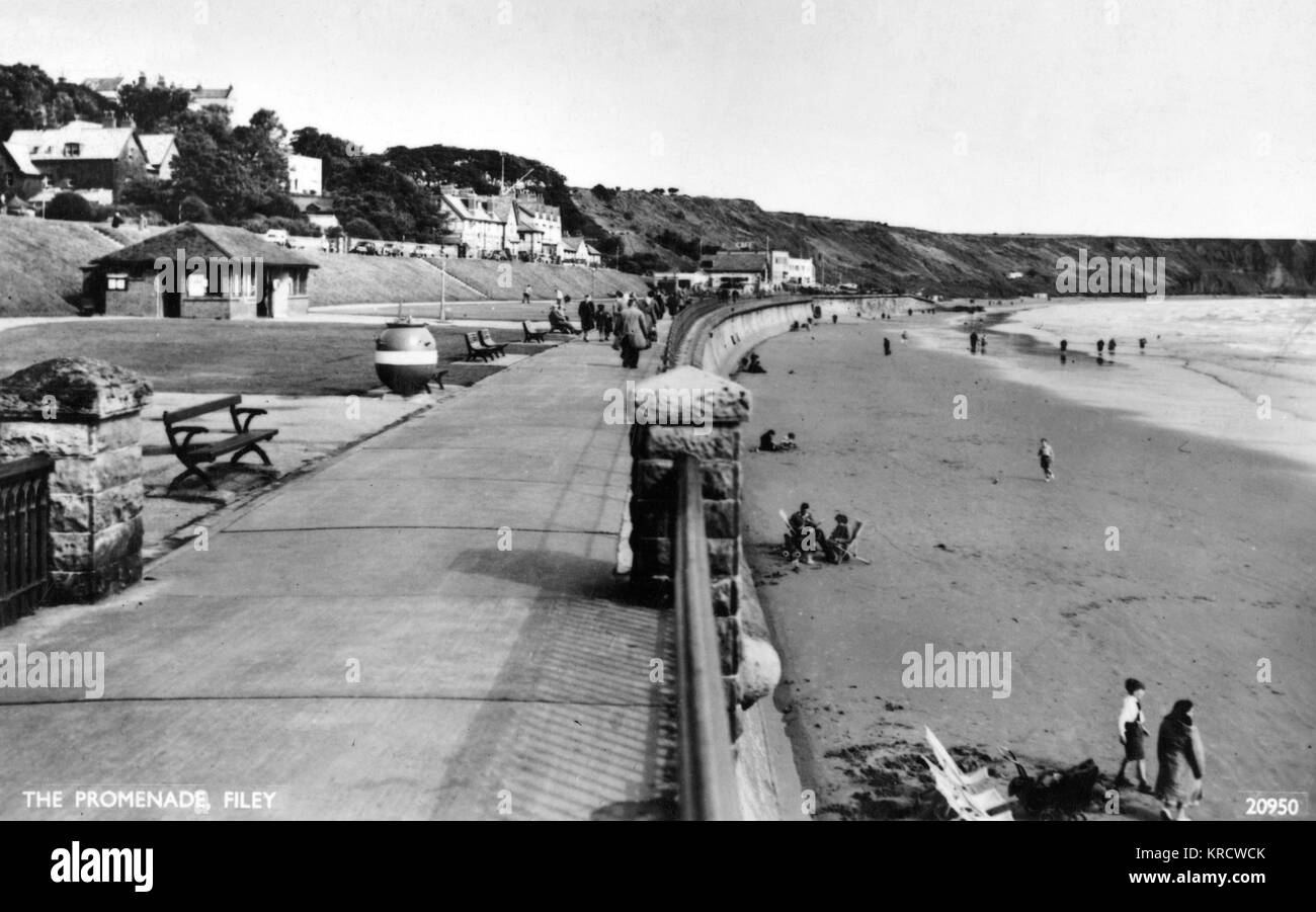 View along the Promenade at Filey, North Yorkshire, with a few people on the beach. Date: 1940s - Stock Image