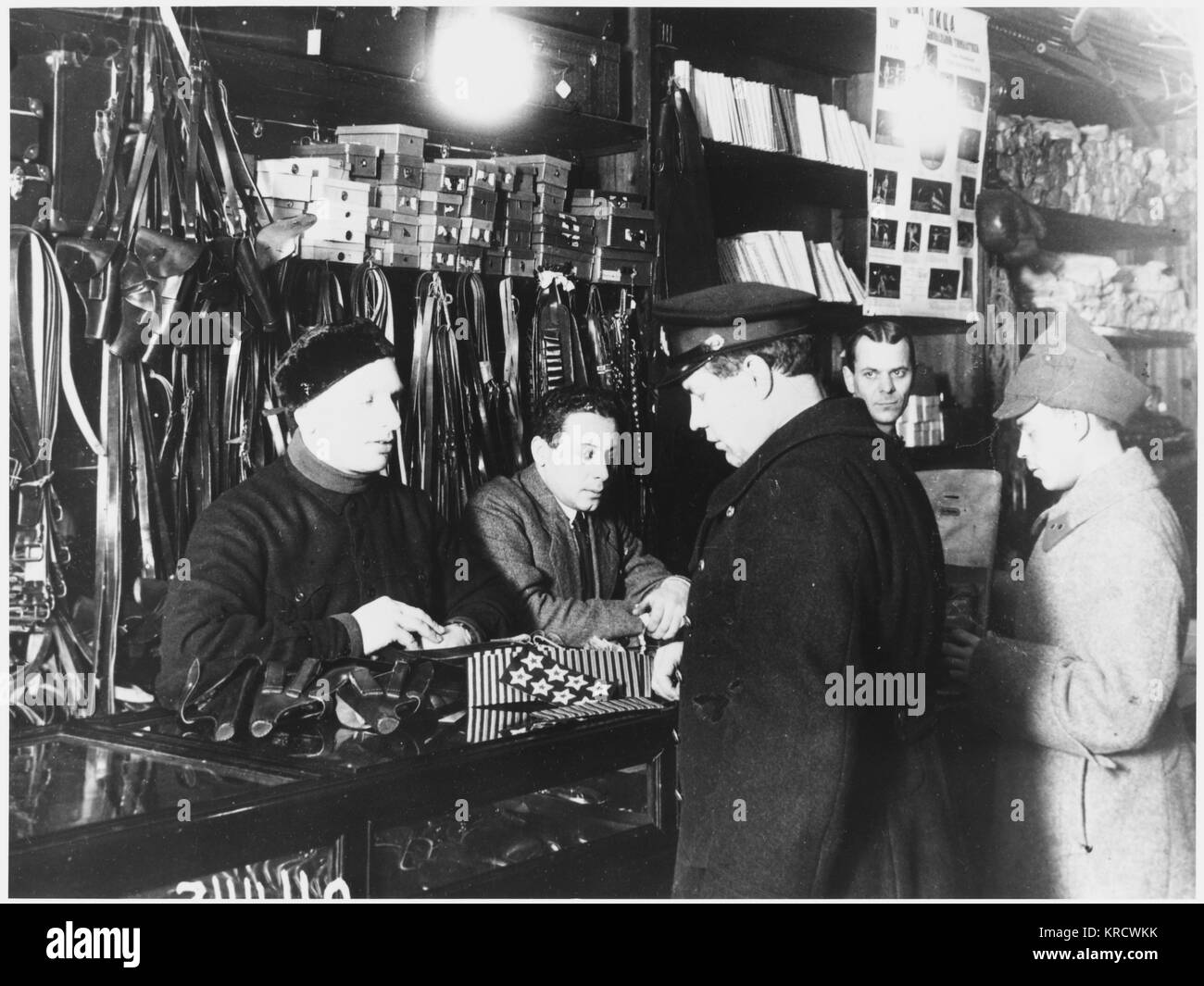 Customers examine goods over the counter in the military goods section of a Leningrad department store Date: 1928 - Stock Image
