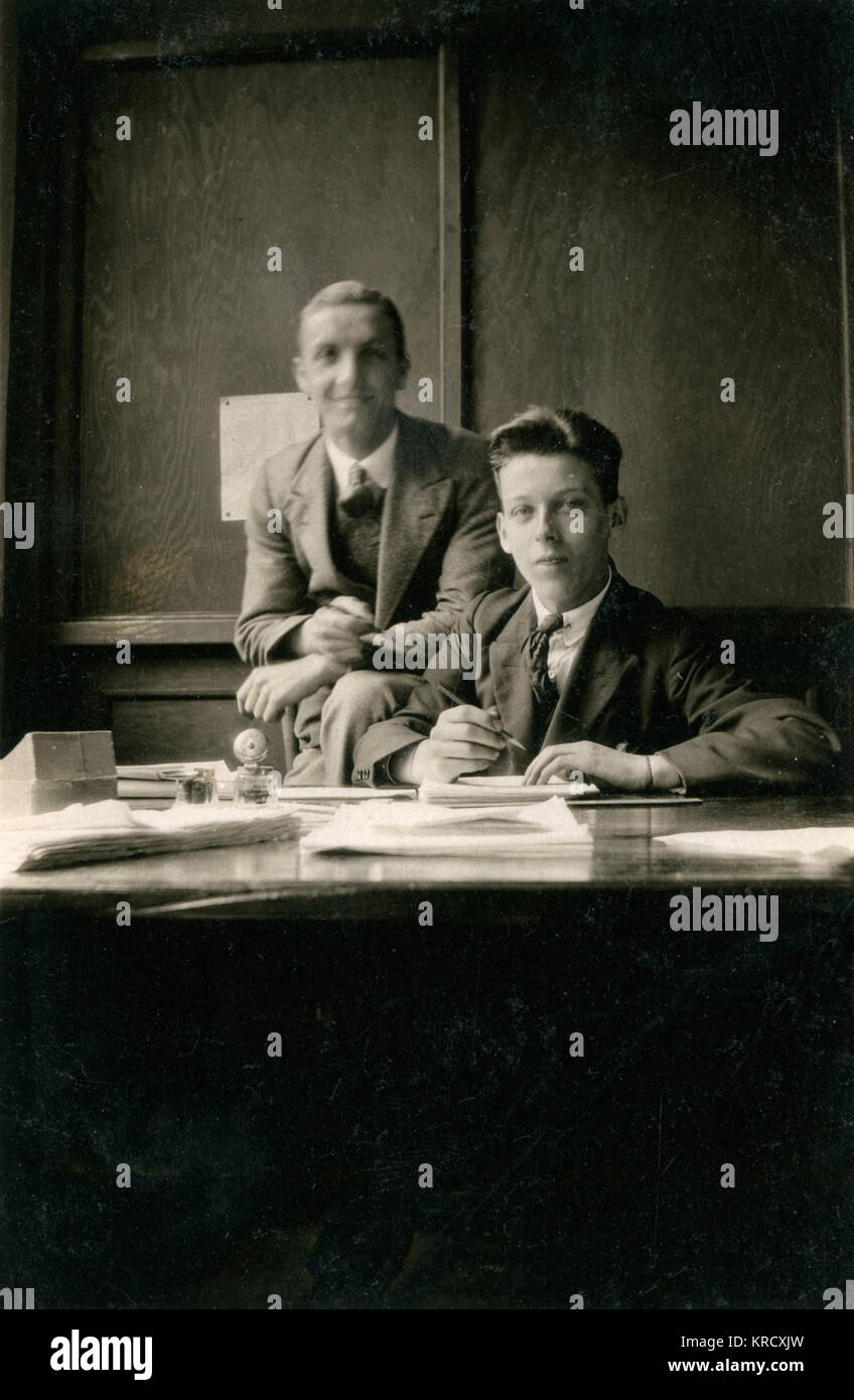 Two young clerks in an office pose for their photograph.        Date: circa 1930s - Stock Image