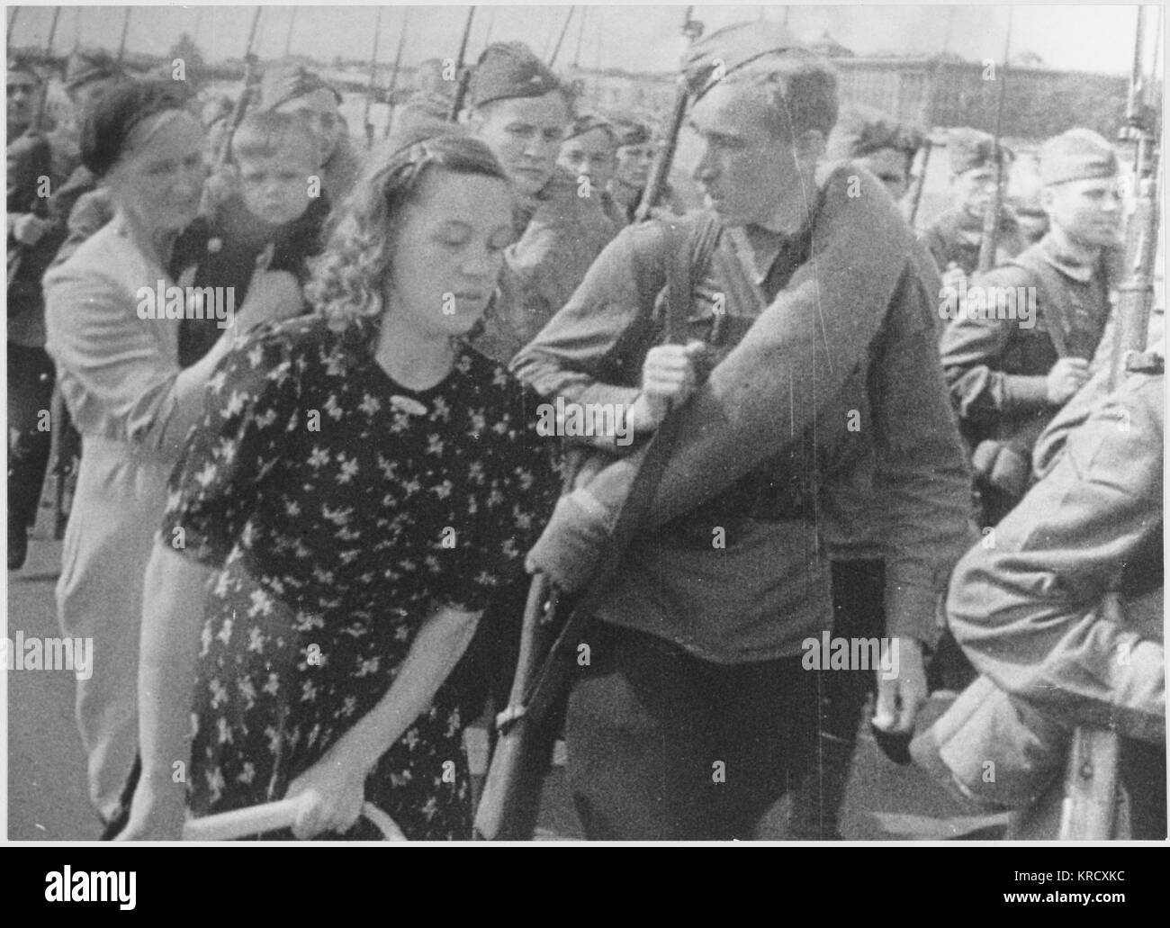 Russian soldiers leave for the  front.  A young woman walks  beside her man as she says  goodbye.       Date: 1939 Stock Photo