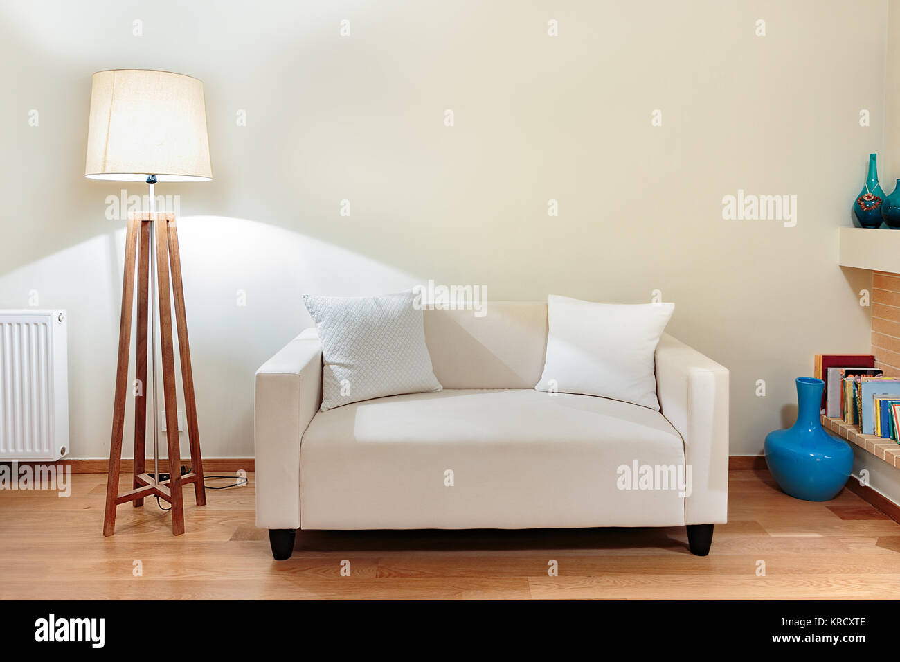 A small two seater sofa with two little pillows and a wooden base lamp on an oak floor. - Stock Image