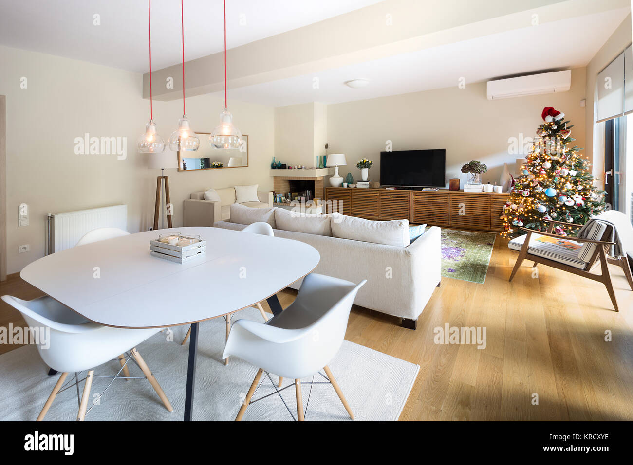 A large living  - dining room with a white table, four white eiffel armchairs, a mid century style wooden arm chair, - Stock Image