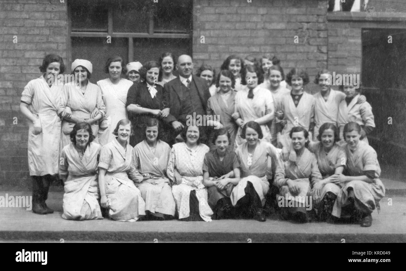 A group of female factory workers pose for a photo with  their male boss at Burroughs & Sturgess, Frederick - Stock Image
