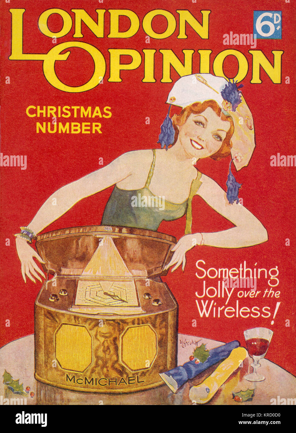 A jolly looking woman wearing  a party dress and paper hat  opens the top of an old  wireless set, ready to play - Stock Image