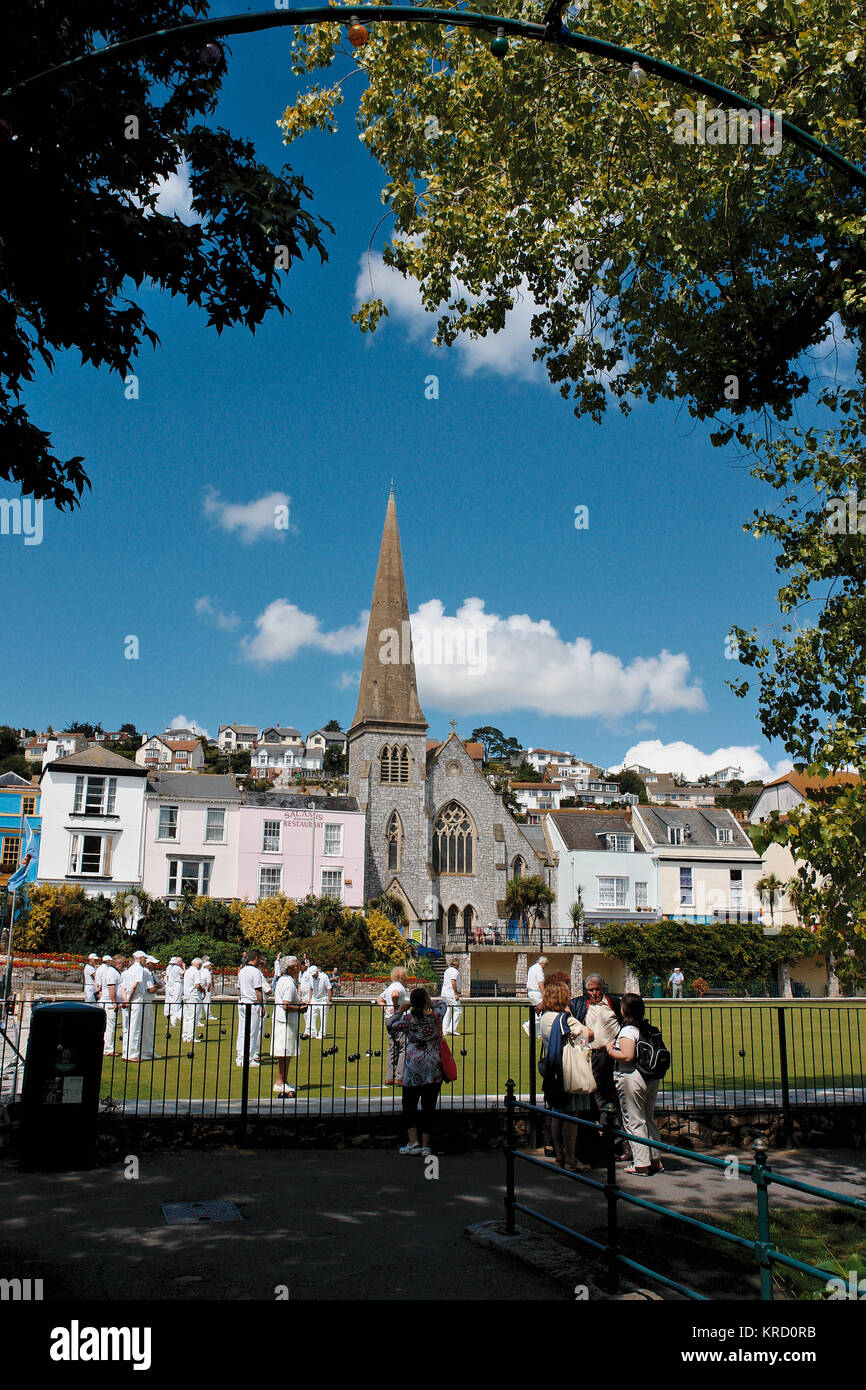 A game of bowls takes place on a green in Dawlish, Devon, overlooked by a church with a spire.  The players are - Stock Image