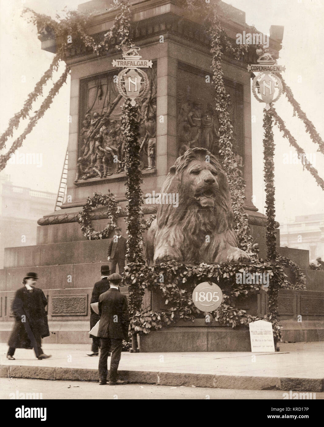View of one of the lions at the foot of Nelson's Column in Trafalgar Square, Central London, at the time of - Stock Image