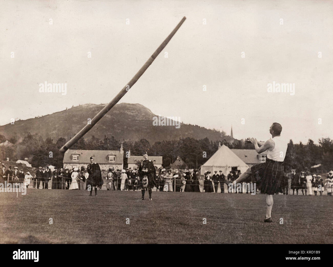 Scene at the annual Braemar Gathering, showing McIntosh of Partick tossing the caber.  Braemar in Scotland holds Stock Photo