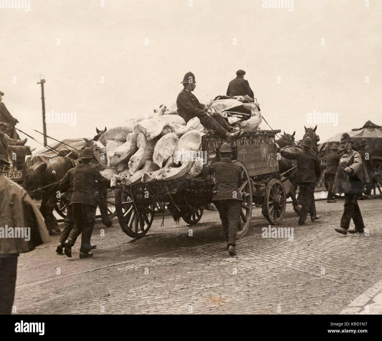 Policemen accompany a cart carrying goods across the bridge at Canning Town, near the London Docks in East London, - Stock Image