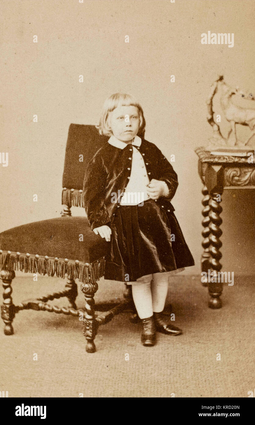 A little Victorian girl wearing a matching velvet jacket and skirt, leaning against an upholstered chair in the - Stock Image