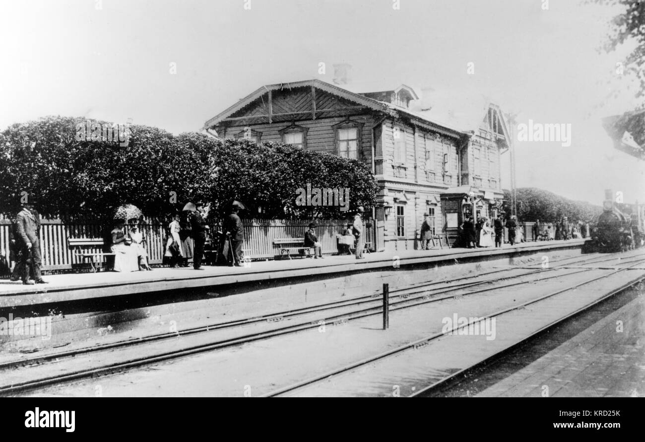 A view of a railway station building and passengers standing on the platform waiting for the approaching steam train, - Stock Image