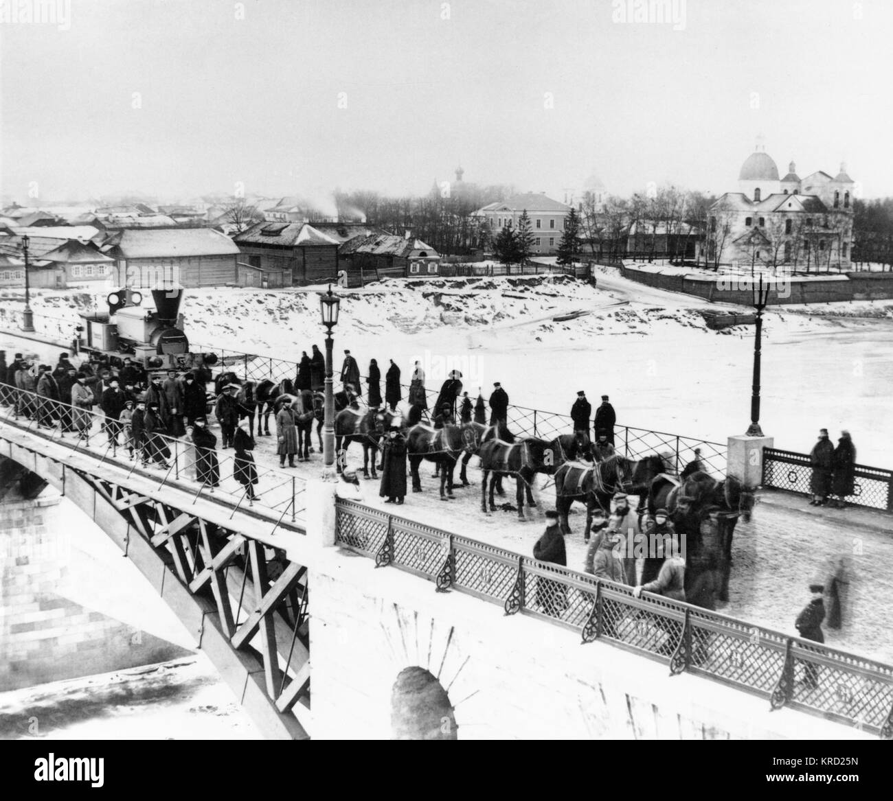 View of a bridge over which a locomotive is being pulled by fourteen horses to be delivered to the Orlovsko-Kitebskaya - Stock Image